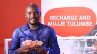Mugumya Hassan, Business man from Katooke pose for a photo with his money he won in the Recharge Promotion.