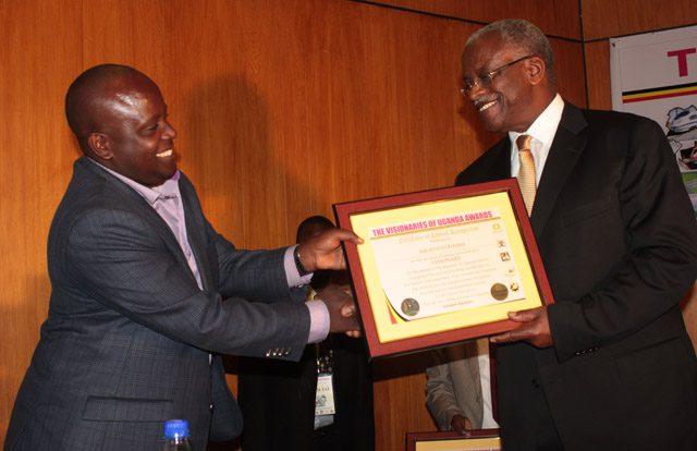 Apollo Kibira receiving his award