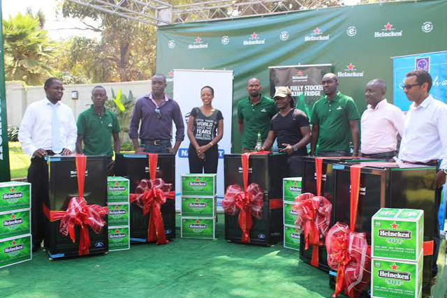 Juliana Kagwa (3rd from Left) Heineken Country Manager with other Heineken staff give the winners their fully stiocked fridges
