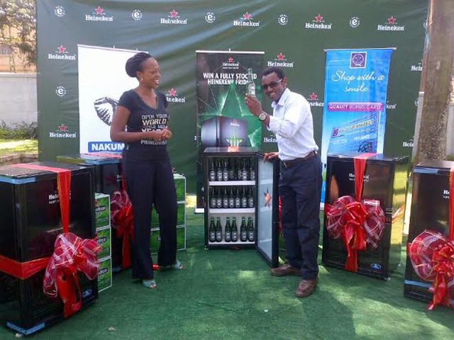 Juliana Kagwa Heineken Country Manager with other Heineken staff give the winners their fully stiocked fridges