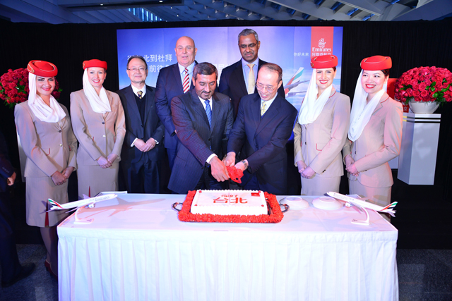 Officials from both parties cutting a ceremonial cake to mark the inaugural flight