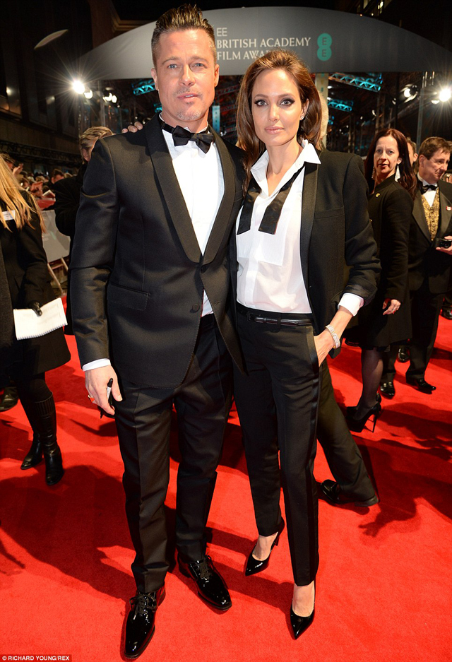 His and hers; The only thing distinguishing Brad Pitt from Angelina Jolie was an unbuttoned collar as the couple arrived on the red carpet at the 2014 EE BAFTAs in matching black suits on Sunday night