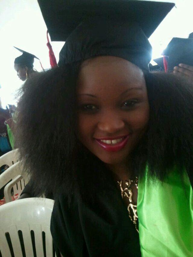 Milka Irene putting on her graduation gown