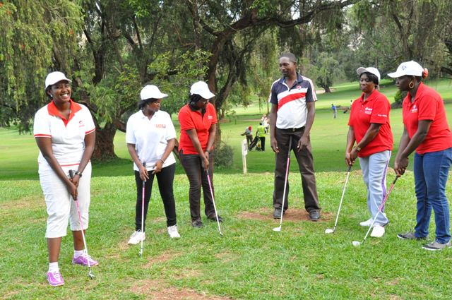 Ladies being trained on how to handle their clubs and take shots