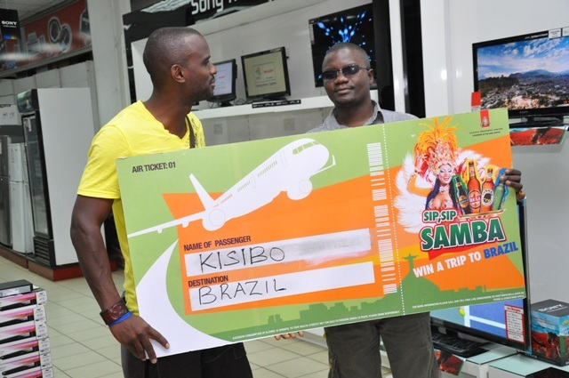 Musa Kisibo (R), an employee of Uchumi Super Market receives an air ticket to Brazil from Justin,show host of the on going Sip Sip Samba promotion. A total of 40 lucky people will win tickets to Brazil
