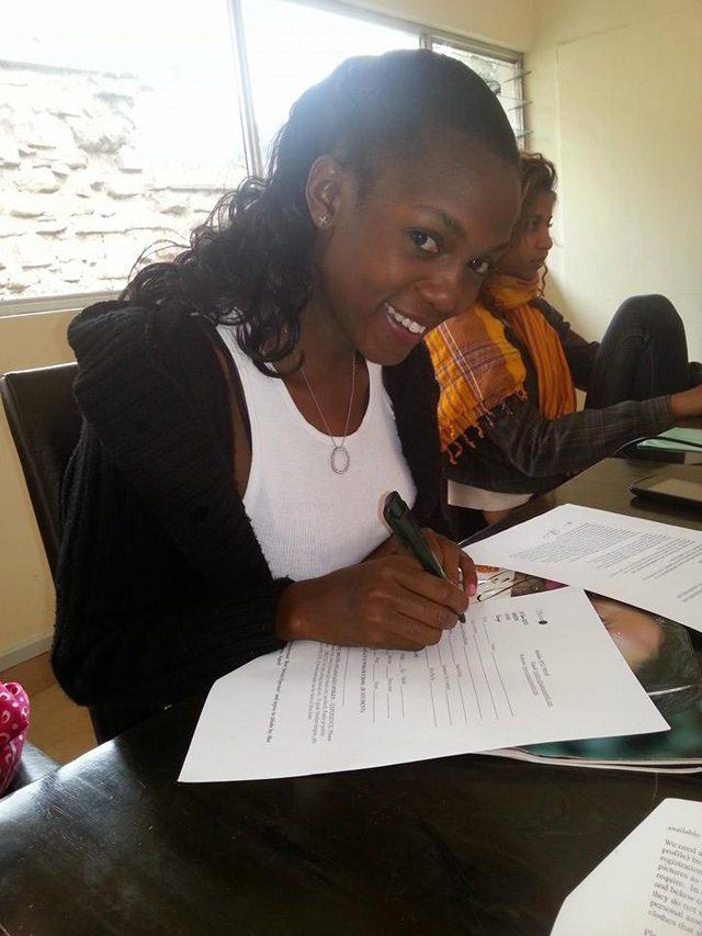 Nina Mirembe signing the deal