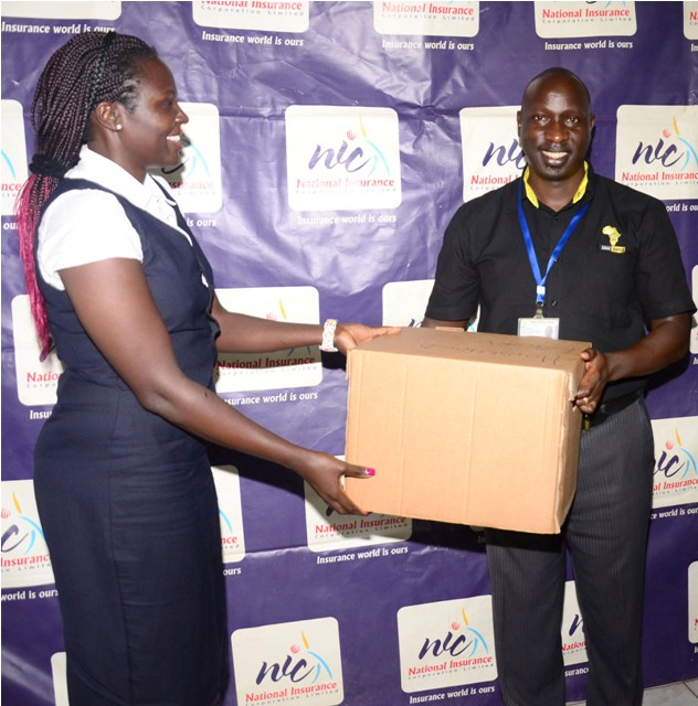 Ms Pamela Abonyo, the NIC's senior manager corporate communications, hands over an assortment of items to Dr. Eddie Mwebesa, the clinical director and member of the Chief Executive Team at Hospice Africa Uganda, in Kampala on Wednesday.  Under the partnership, NIC staff will volunteer at the HAU offices and run donation drives within the organisation and among the NIC community on social media