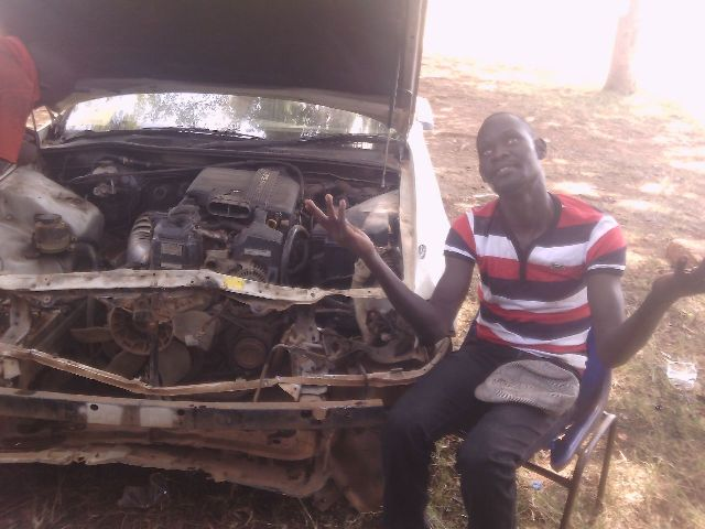 Prince Ehmah pointing to heaven beside his damaged car