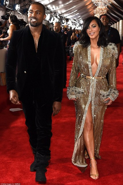 Kim Kardashian oozed sparkle as she wore what looked to be a silver and gold robe. The outfit was attached only in the waist area and looked like it could easily slide off; by her side was husband Kanye West
