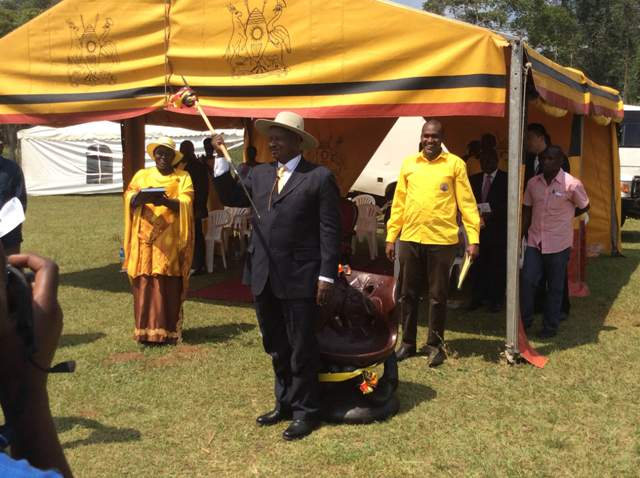 Frank Tumwebaze (in yellow) with his boss President Yoweri Museveni at a recent function in Kamwenge. He has called on Besigye to quit politics of doom