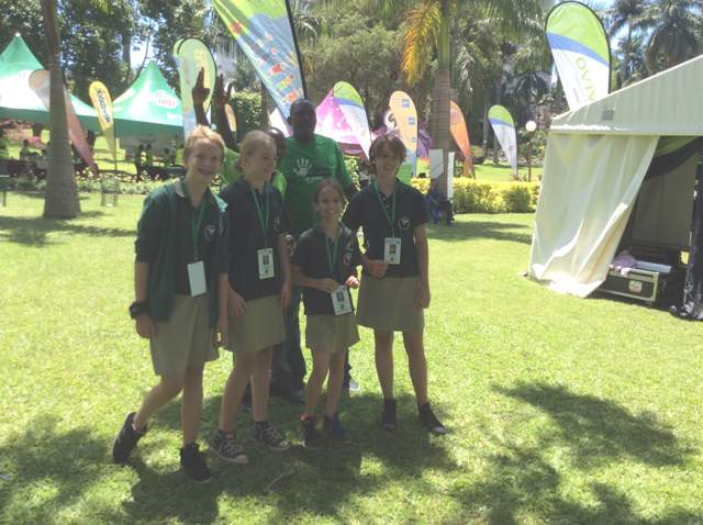 Joseph Masembe of Little Hands Go Green pose with some of the children at the conference
