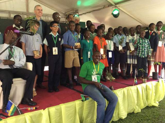 Little Hands Go Green CEO, Joseph Masembe (seated) pose for a group photo with digitories and children