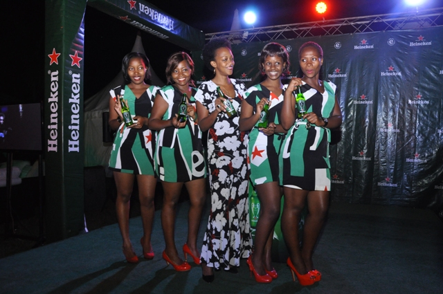 Juliana Kagwa (C) Heineken Uganda Country Manager display the limited edition bottles to the cameras at the launch