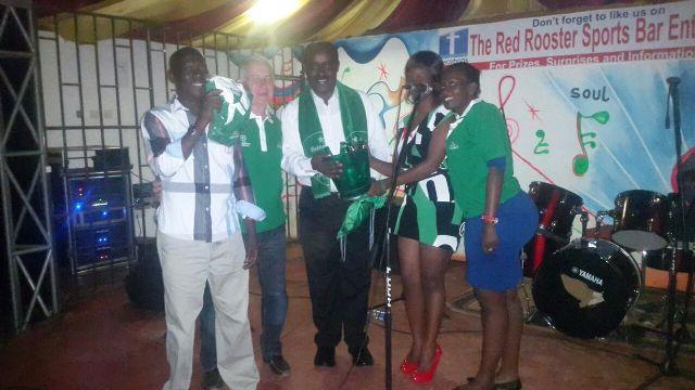 Heineken Sales consultant rewards Mr.  George Wairubi with Heineken merchandise at Red Roosters in Entebbe