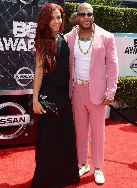 Flo Rida rocked a bubble-gum pink suit as he posed with his stunning flame-haired date