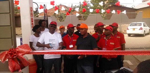 Total Uganda sales Manager Allan Omuron cuts ribbon with Total staff during the official launch of the new station in Najjera last Saturday