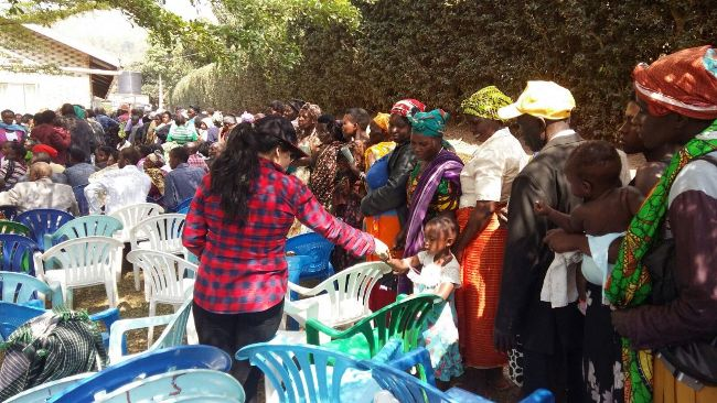 Locals queue for free medical check up as Sheena serves a kid