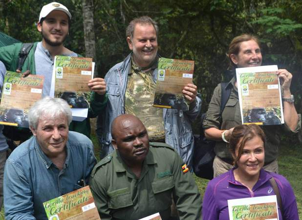 Tourists display their certificates after successfully tracking gorillas at Bwindi impenetrable national park recently (standing middle) is Molina