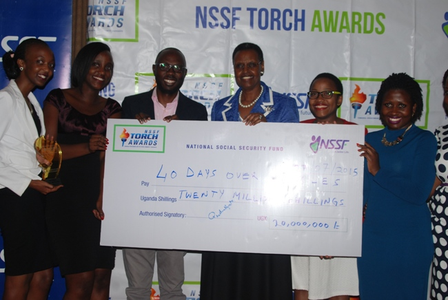 First lady Janet Museveni hands over a dummy cheque worth Shs20m to Esther Kalenzi of 40days 40smiles and her team as the national winner of the torch awards, as NSSF MD Richard Byarugaba and NSSF Deputy