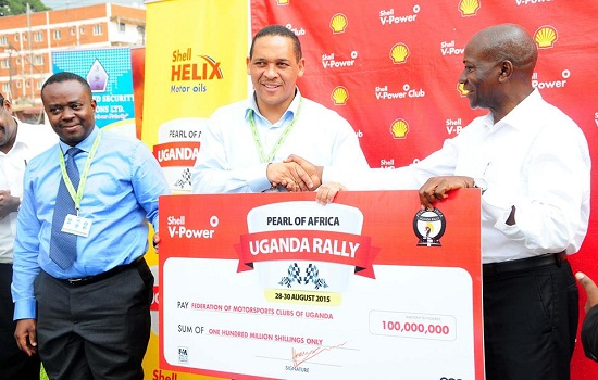 Vivo Energy Uganda MD Hans Paulsen (C) with rally officials showing the damn cheque