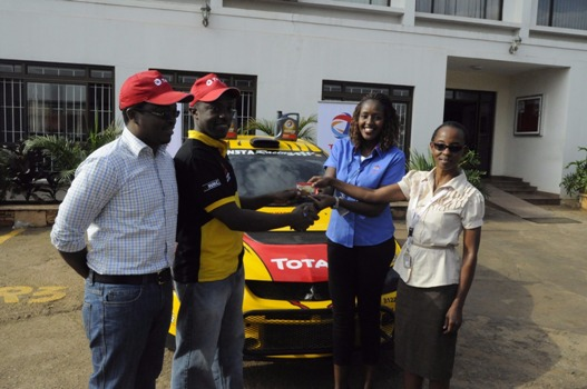 Total Uganda Marketing and Communications Manager Lois Tusiime (R) hands over a fuel card to rally driver John Constantine during the press conference at Total Uganda Head office today
