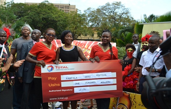 Total Uganda Marketing and Communication Manager Lois Aber Tusiime (L) handsover a dummy cheque worth Shs100m to KCCA Executive Director Jennifer Musisi (M) as a sponsorship package for the Kampala City Festival due to take place on 4th October