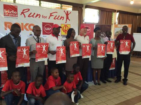 Sponsors, some members of Kids of Africa and their management pose with banners for November  8th Run for Fun