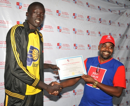 Oscar Kamukama hands over a certificate to one of the winners