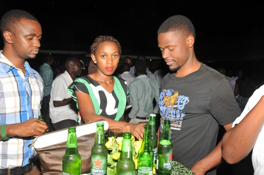 one of the ushers serving Heineken lovers with the new bottle