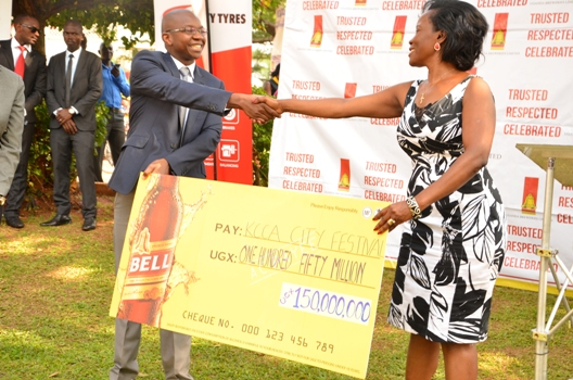 Mr. Nyimpini Mabunda, Managing Director Uganda Breweries Limited hands over a dummy cheque to Ms. Jennifer Musisi, Executive Director Kampala City Council Authority (KCCA)