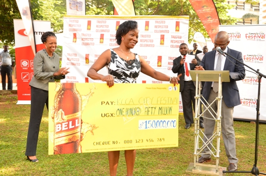 Ms. Jennifer Musisi, Executive Director of the Kampala Capital City Authority (KCCA) displays the cheque. Looking on is Ms. Juliana Kagwa, Marketing Director UBL