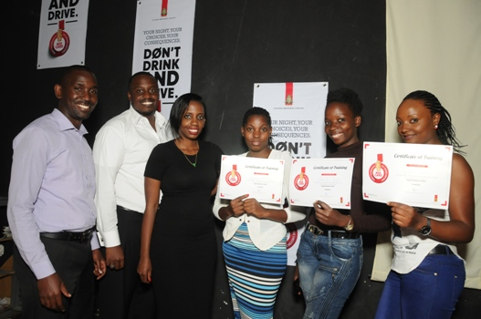 (L-R) UBL's David Onyango, Ronald Tumwizere and Rhona Arinaitwe pose for a photo with some of the bar tenders that completed the responsible serve training