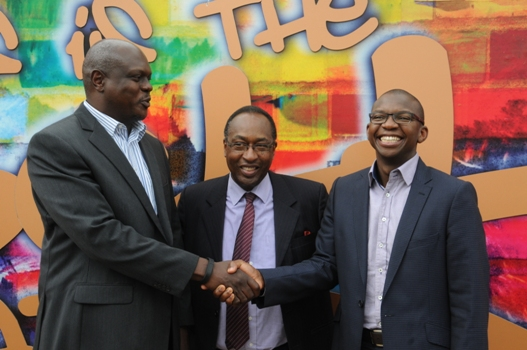 Mr. Mark Ocitti Ongom and Mr. Nyimpini Mabunda shake hands at a press briefing at which Uganda Breweries Limited (UBL) announced a change in leadership. Mark replaces Nyimpini as Managing Director of UBL effective August 1. Centre is the Board Chairman, Dr. Allan Shonubi