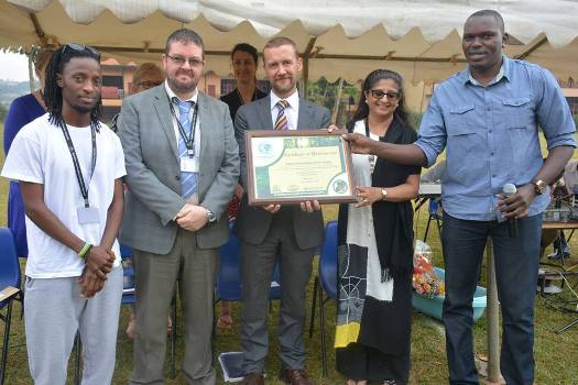 Uganda's Little Hands Go Green boss Joseph Masembe (R) hands over the certificate to Rainbow International School Uganda management