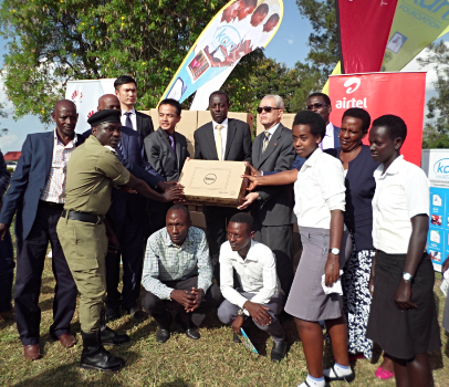 Minister of ICT Hon. John Nasasira (Middle), Huawei Managing Director Stanley Chyn(Left) and Chinese Ambassador H.E Zhao Yali (Right) hand over a PC to officials from Karo Secondary School in Kiruhura District