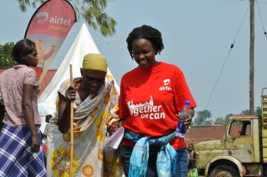 An Airtel staff member happily leads the old lady to the physician