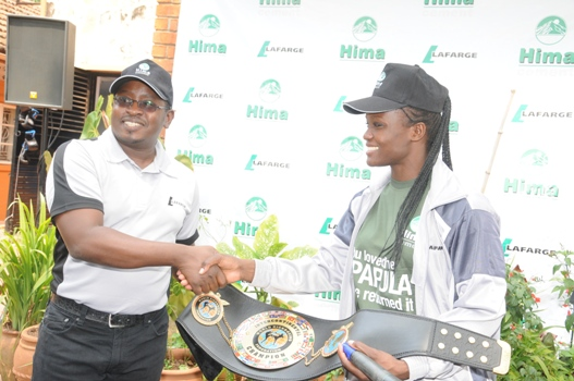 HIMA Cement's Marketing Director Allan Ssemakula shakes hands with with Patricia Apolot the current Female Lightweight World Kickboxing Champion during a press briefing
