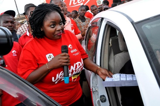Airtel's head of Brand and Communications, Remiie Kisakye hands over the car's log book to Grace Twongyeirwe