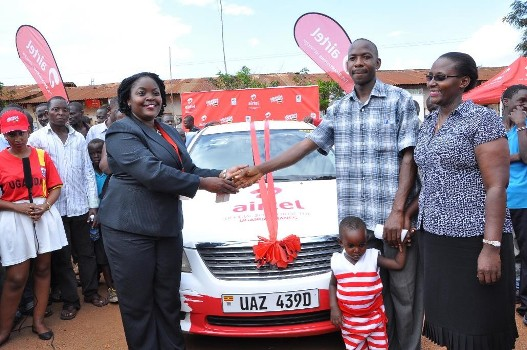 Kawooya Amiri Sunday the third car winner of Mujje Tulumbe  pomotion being congratulated by Airtel Uganda Head of Brand and Communications Remmie Kisakye as his family looks on
