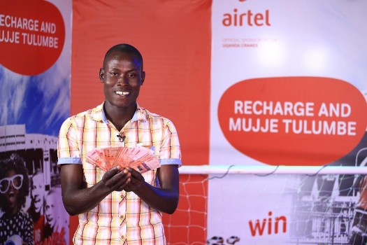 Kayizzi Hamis, Mechanic from Kavulu with the money he won in the Recharge Promotion pose for a photo