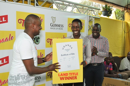 (L-R) Mark Mugisha, Head of Beer at Uganda Breweries Limited (UBL) hands over a dummy title to Aloyzious Kizza, 21 years old, who emerged winner of a plot of land in the ongoing Tubbaale promotion