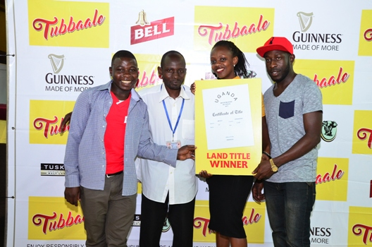 (L-R) Winners of land receive a dummy title. Makenya Stephen, Walusimbi Joseph, Cathy Twesigye, Guinness Activation Manager and Serunjogi Julius