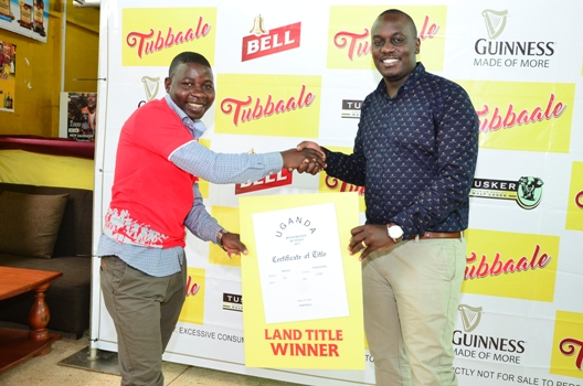 (R-L) Brian Seruyiggo, Customer Marketing Manager, Bell Lager hands over a dummy title to Makenya Stephen, a Bar and Restaurant Cashier who emerged winner of a plot of land in the ongoing Tubbaale promotion