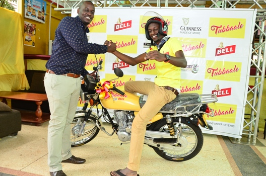 (L-R) Brian Seruyiggo, Customer Marketing Manager-Bell Lager congratulates Muwanika James on participating and winning a motorcycle in the Tubbaale promotion