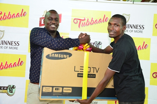 Murungi Rogers (R), a second-time winner in the UBL Tubbaale promotion receives his 32-inch flat screen TV from Brian Seruyiggo (L), Customer Marketing Manager-Bell Lager