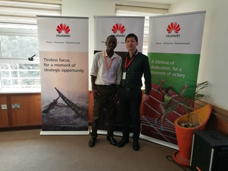 Mr. Benjami, the Human Resource Director (R) congratulates Mark Mukiibi (l), intern among those retained for a Job at Huawei.