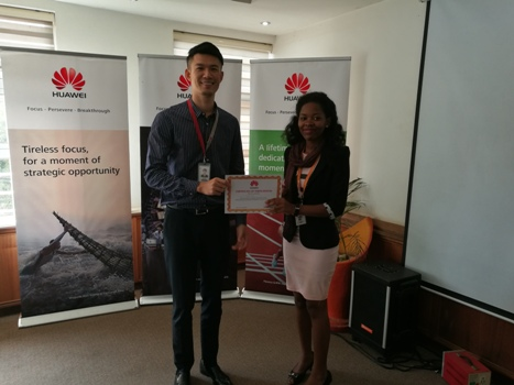 Mr. Tongyunpeng, Huawei's Public Relations Director handing over a certificate of completion to one of the interns