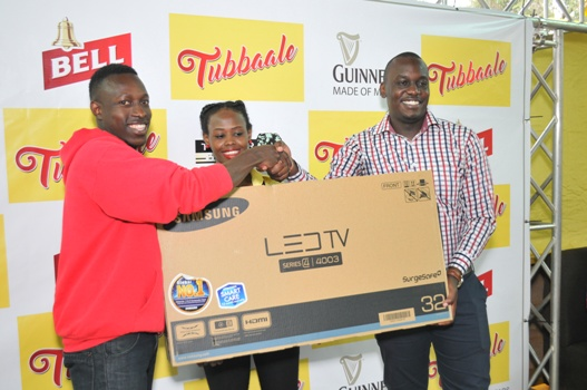 Mukiibi Ronald (L), a winner in the UBL Tubbaale promotion receives his 32-inch flat screen TV from Brian Seruyiggo (R), Customer Marketing Manager-Bell Lager