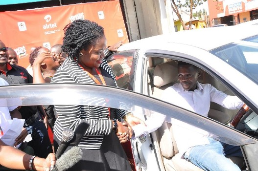 Remmie Kisakye Airtel's Head of Brand and Communications congragulates Steven Byamukama on his win of the 5th recharge and mujje tulumbe car.