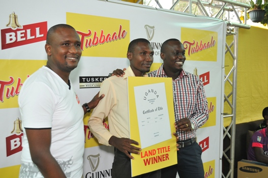 Rogers Murungi, 26,  (centre) says Bell Lager has always been his favorite beer. He won a plot of land in Kampala
